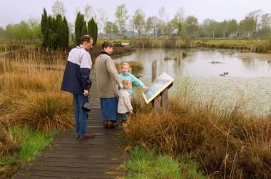 Foto van gezin bij infobord in natuurgebied