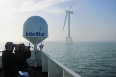 Wetenschappers kijken met verrekijkers naar vogels in windmolenpark op zee