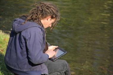 Onderzoeker met tablet naast vijver